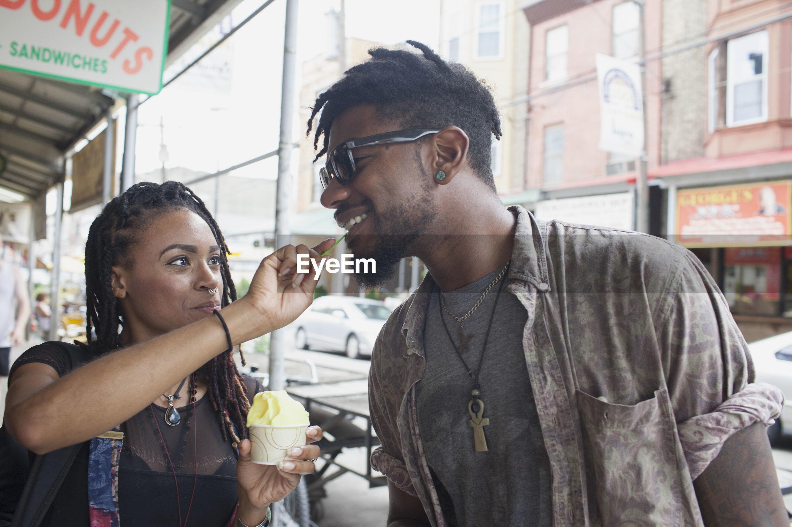 A young woman feeiding a young man frozen yogurt.
