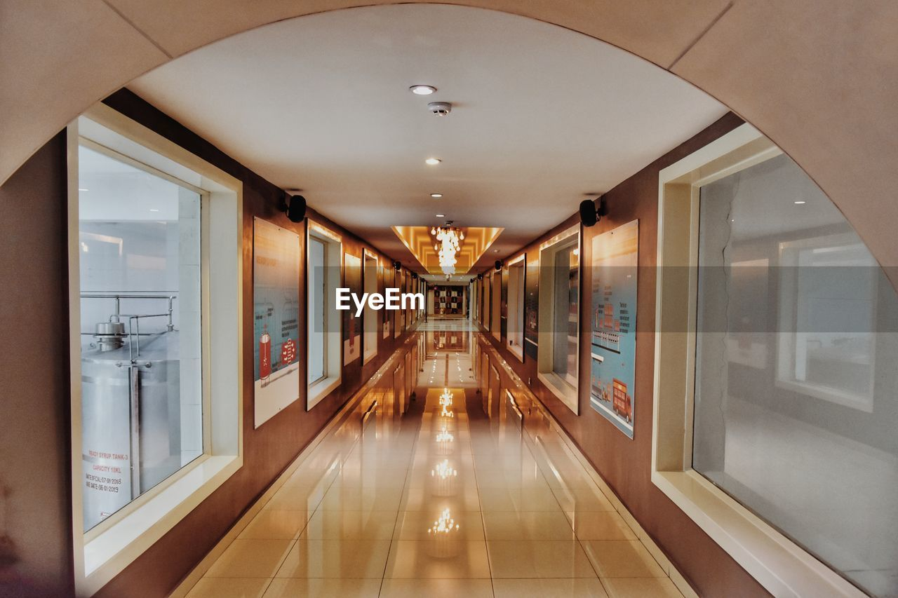 indoors, illuminated, architecture, direction, arcade, corridor, ceiling, the way forward, empty, lighting equipment, building, no people, glass - material, flooring, absence, door, diminishing perspective, built structure, reflection, light, modern, tiled floor, light fixture, clean