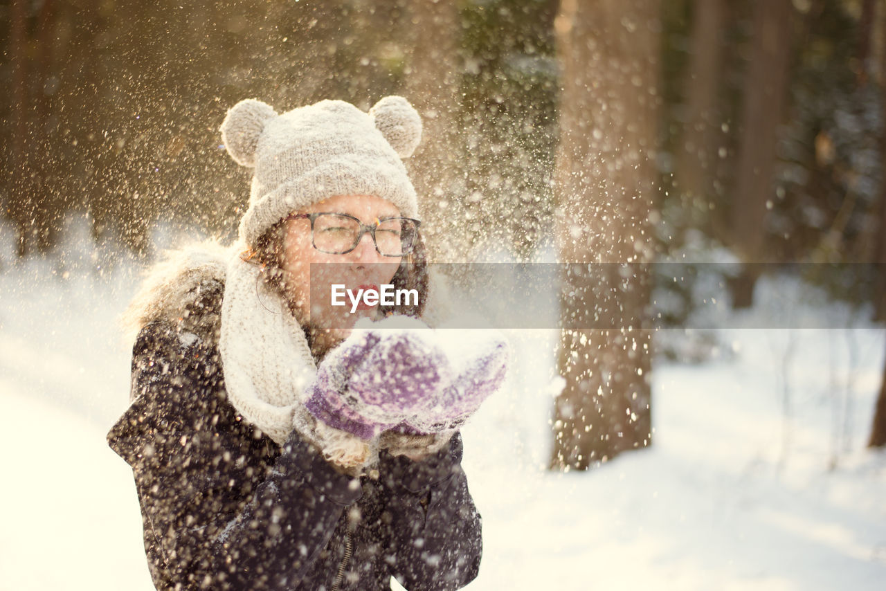 snow, winter, cold temperature, warm clothing, clothing, hat, one person, women, glove, fun, enjoyment, motion, nature, blowing, happiness, adult, waist up, snowball, snowing, scarf, outdoors, hand