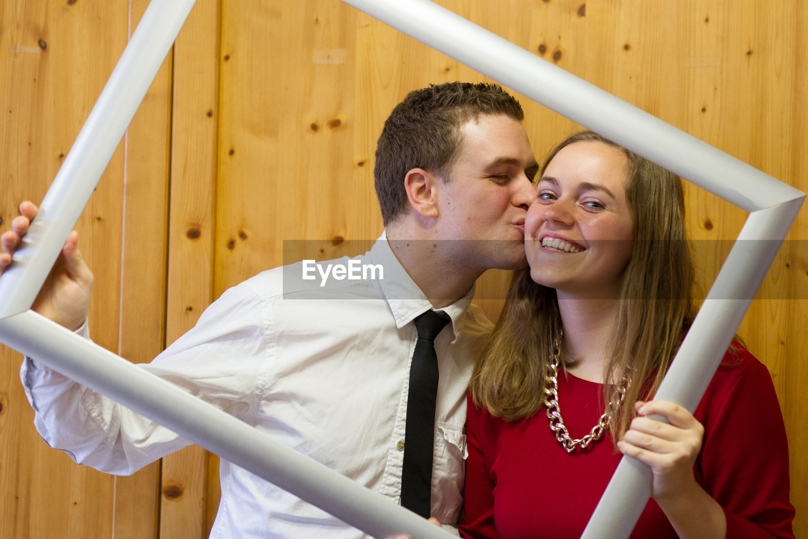Husband kissing wife while holding picture frame against wooden wall