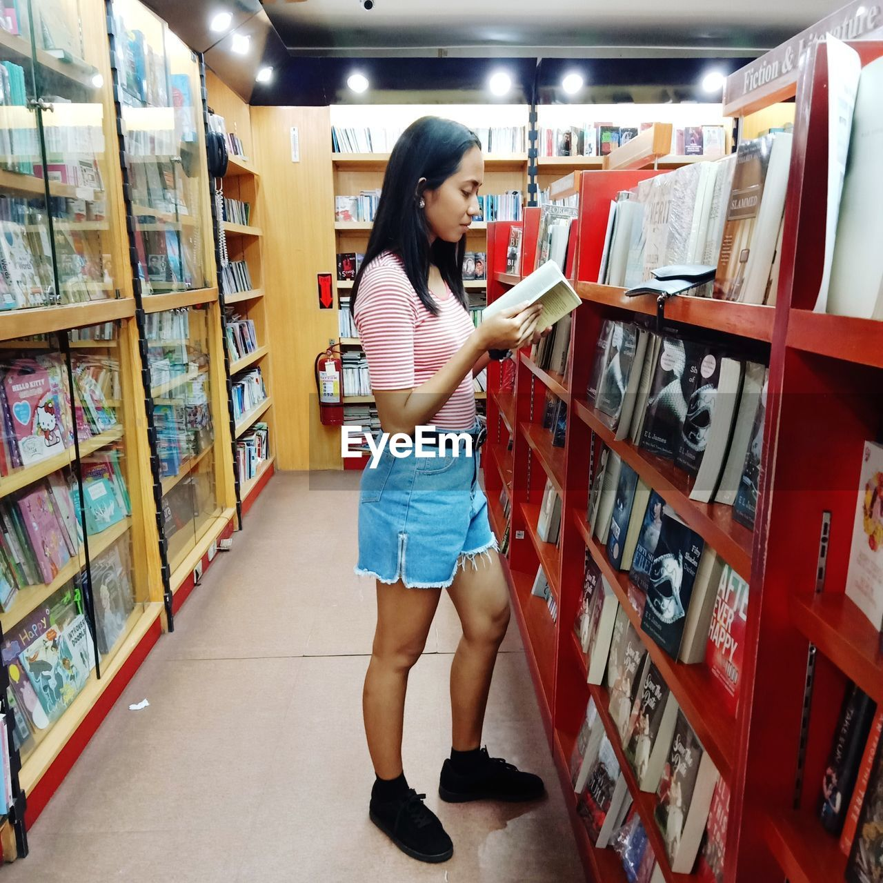 Side view of girl reading in library
