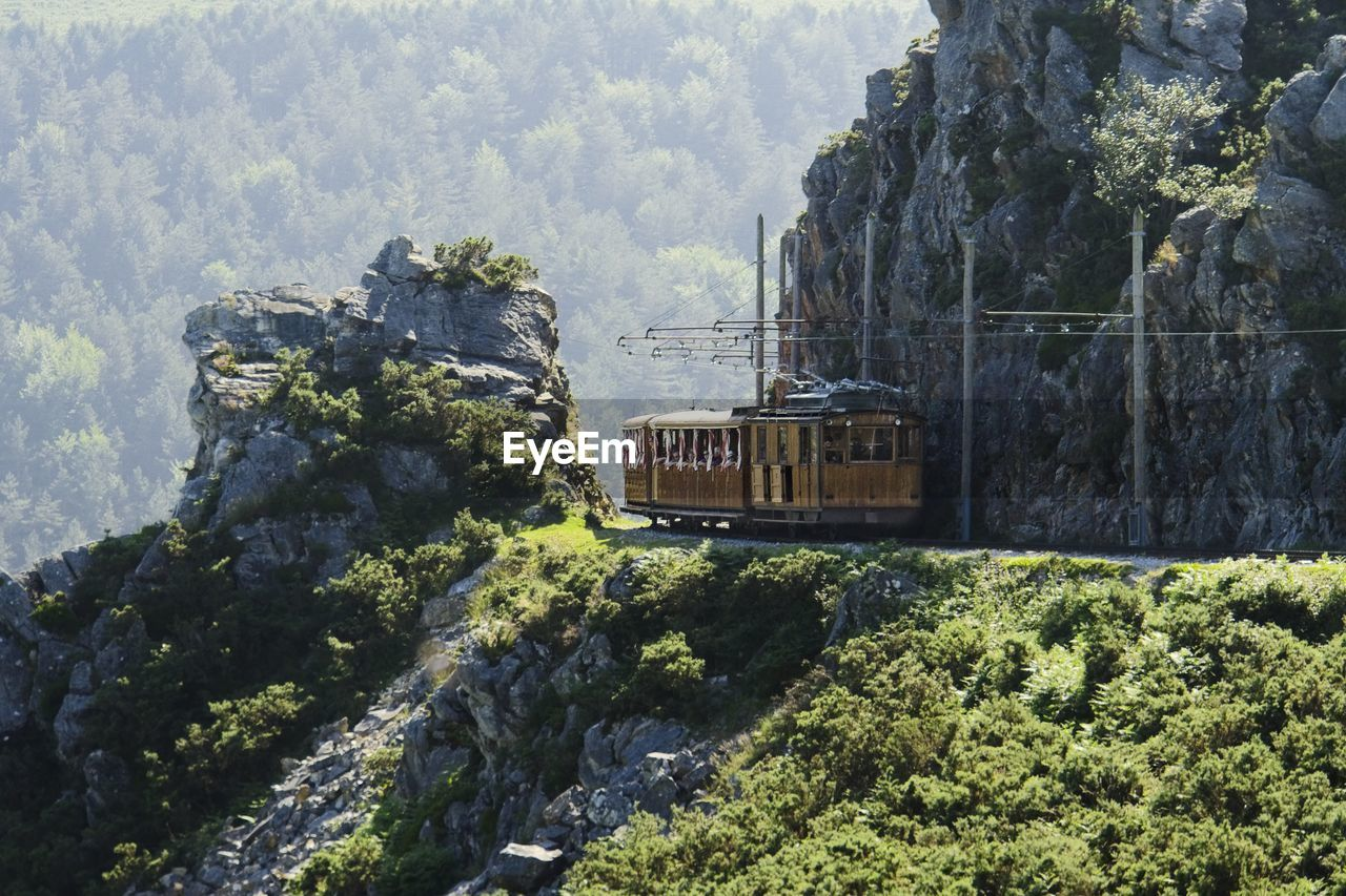 mode of transportation, transportation, plant, nature, train, mountain, rock, public transportation, day, tree, train - vehicle, rail transportation, green color, rock - object, travel, solid, beauty in nature, land, no people, non-urban scene, outdoors