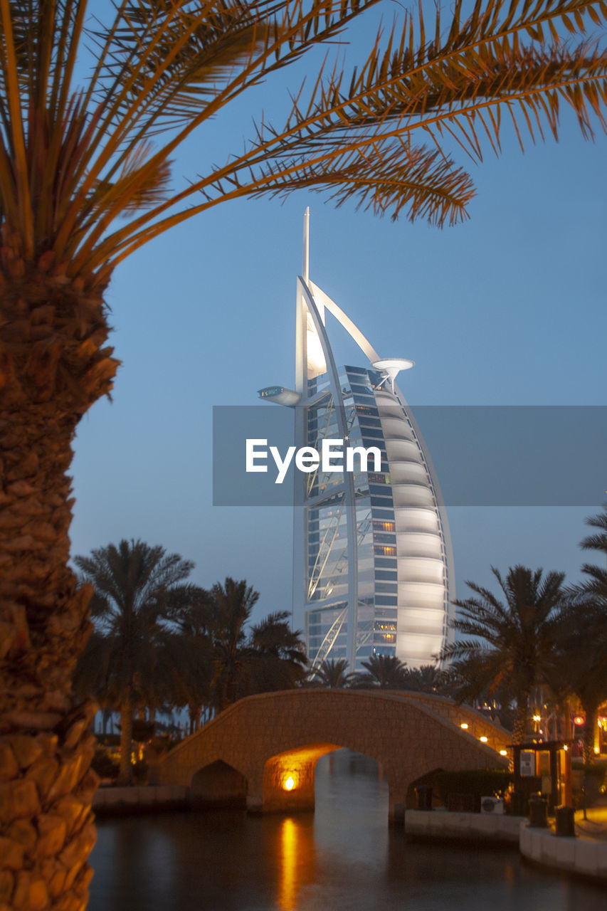 architecture, tree, built structure, sky, plant, building exterior, nature, water, palm tree, travel destinations, no people, illuminated, city, tropical climate, bridge, clear sky, building, travel, bridge - man made structure, outdoors, office building exterior, skyscraper
