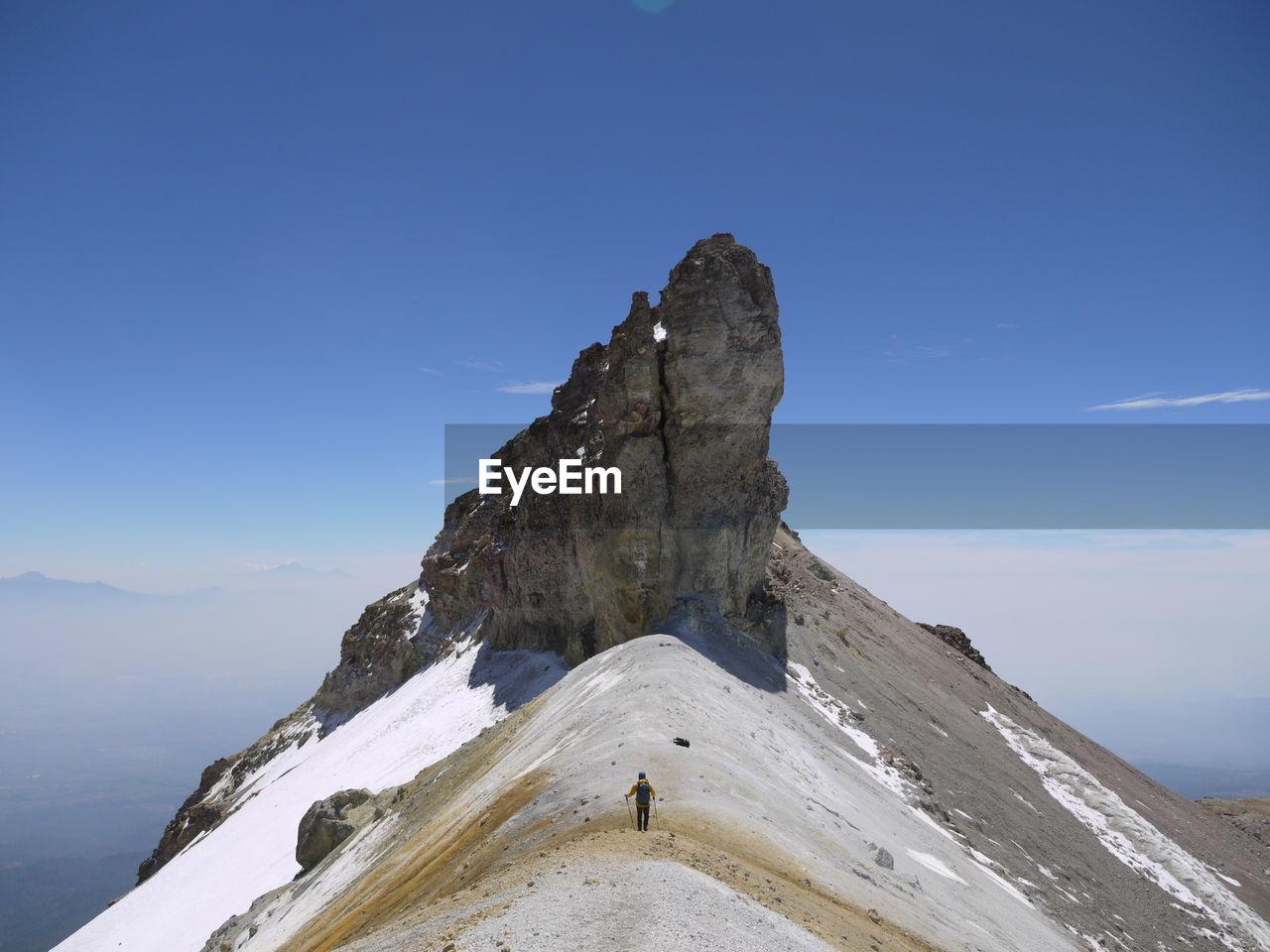Man Hiking On Mountain Peak Against Sky