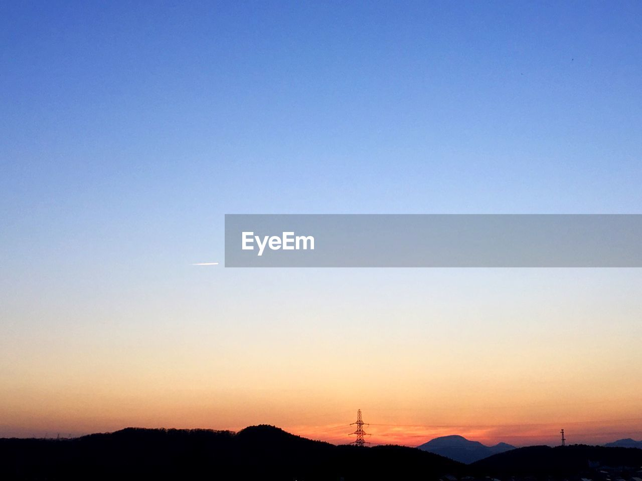 sunset, beauty in nature, nature, silhouette, scenics, tranquil scene, copy space, tranquility, mountain, no people, outdoors, blue, sky, clear sky, landscape, technology, moon, wind power, tree, vapor trail, industrial windmill, day, astronomy