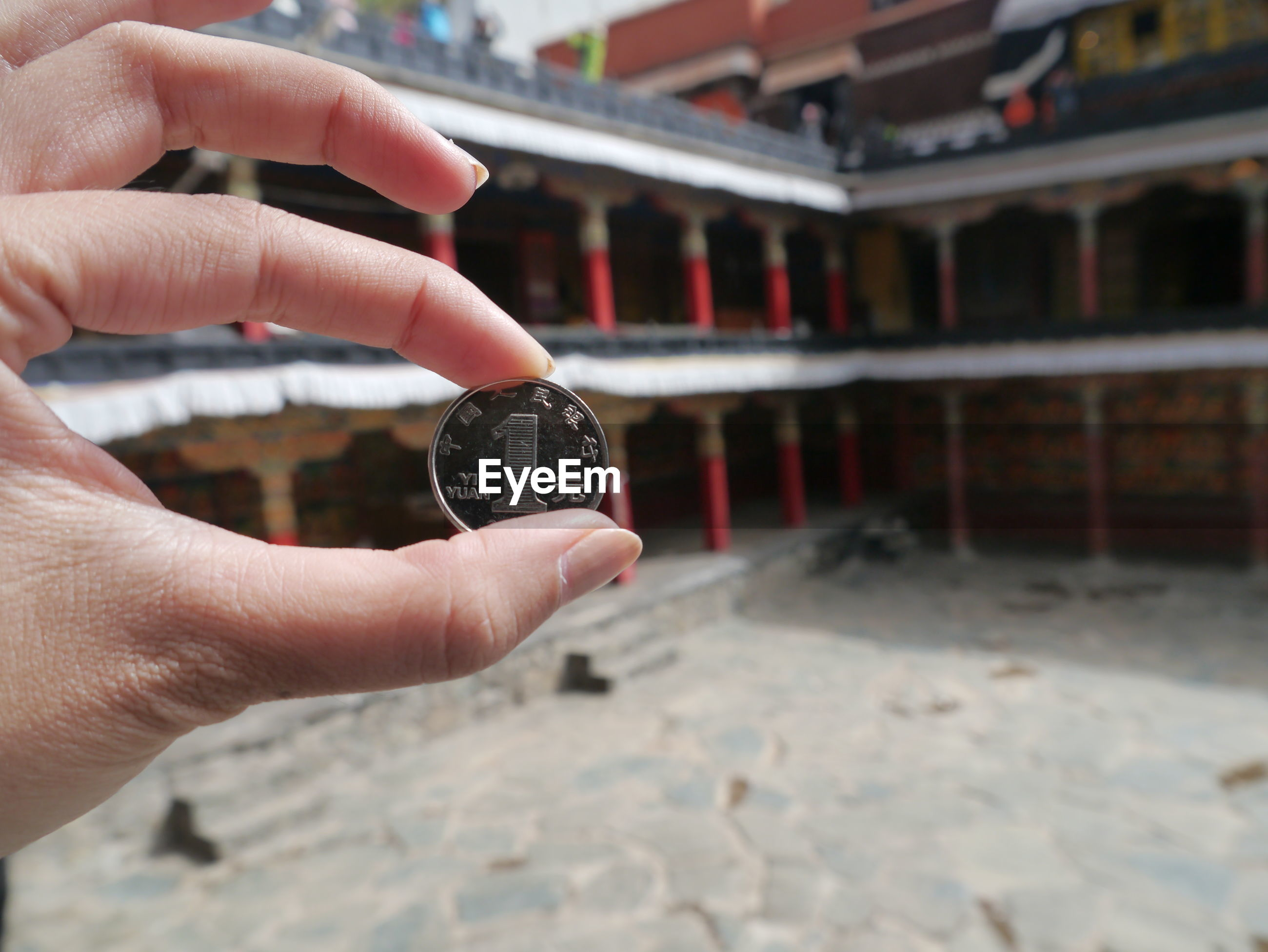 Cropped image of hand holding coin in buddhist temple