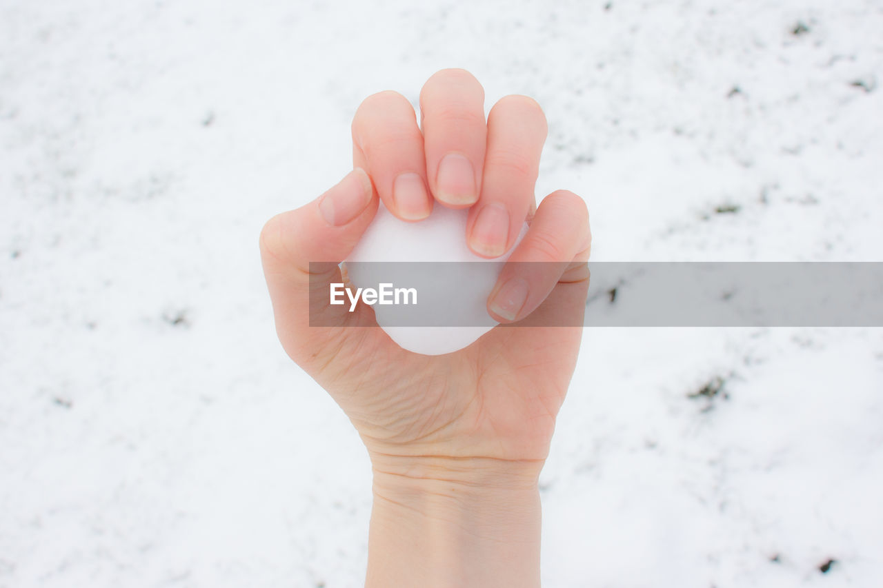 CLOSE-UP OF HUMAN HAND HOLDING ICE