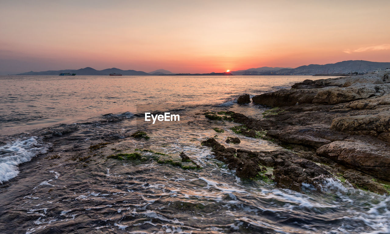 sunset, sea, nature, beauty in nature, scenics, water, tranquility, tranquil scene, sky, sun, rock - object, outdoors, beach, no people, mountain, horizon over water, scenery