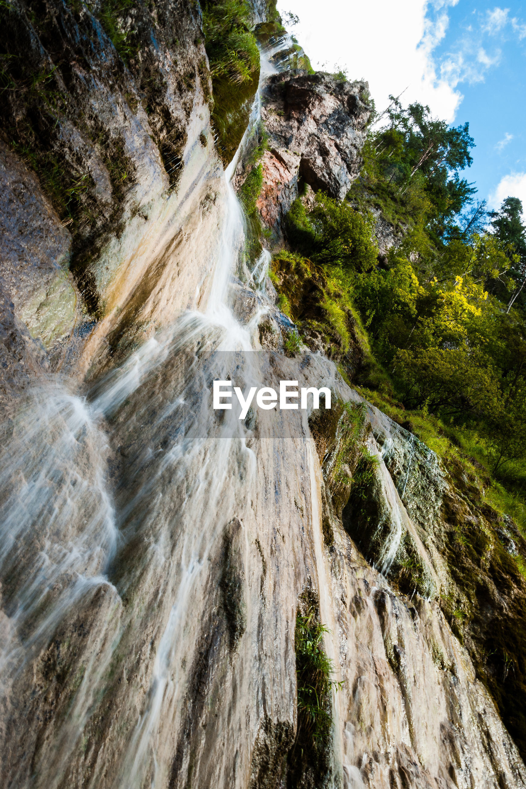VIEW OF WATERFALL IN FOREST AGAINST SKY