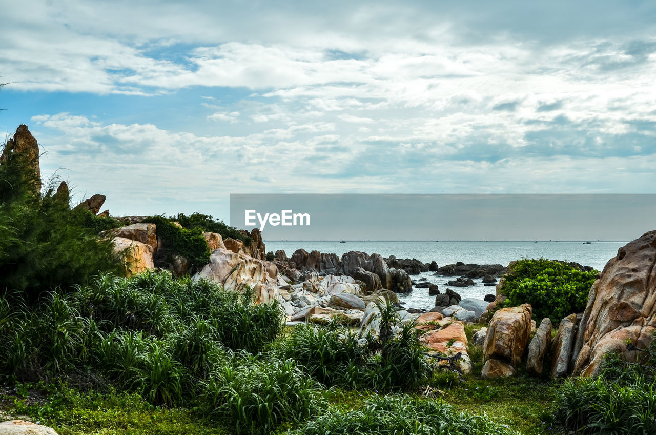 rock - object, cloud - sky, sky, nature, scenics, beauty in nature, tranquil scene, tranquility, rock formation, no people, day, horizon over water, outdoors, water, grass, sea, landscape, tree