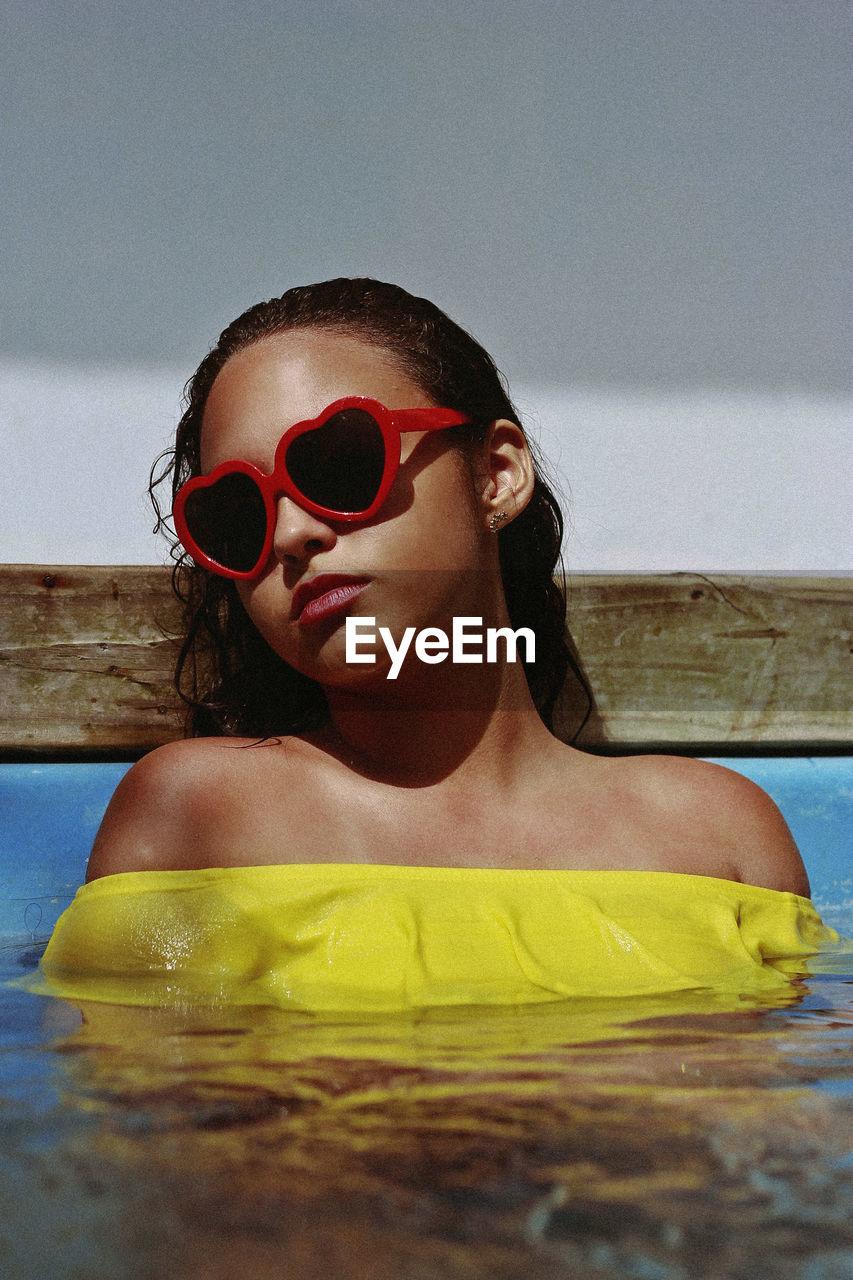 Close-up of teenage girl wearing sunglasses in swimming pool