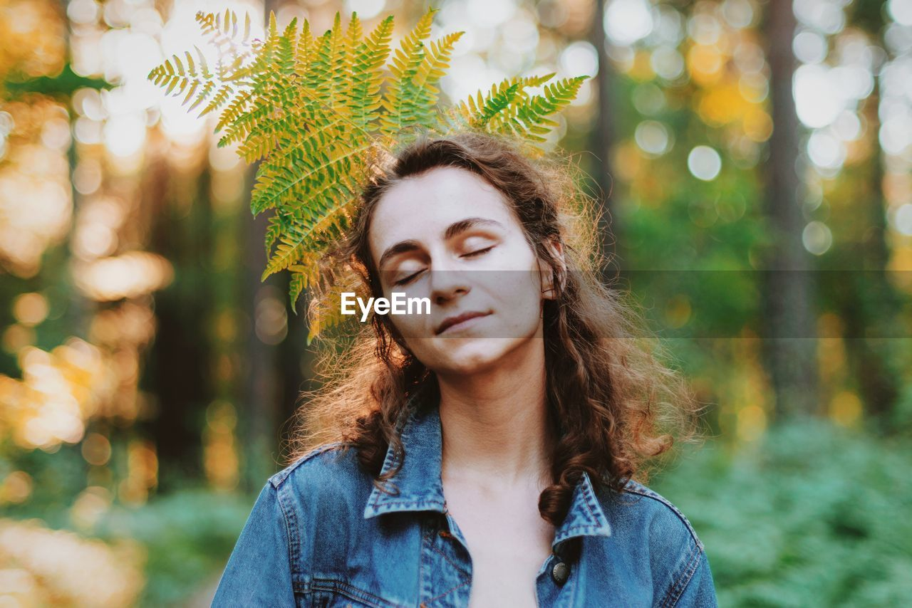Eyes closed young woman with leaves on behind in forest