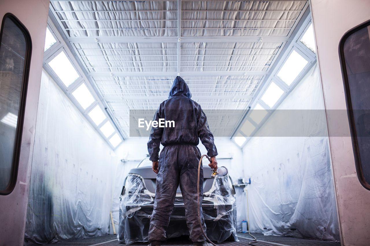 Rear View Of Man Spray Painting Car