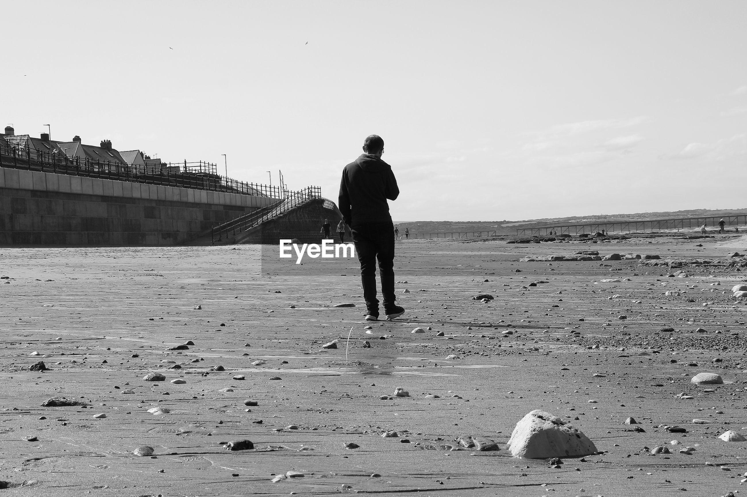 Rear view full length of man walking at beach