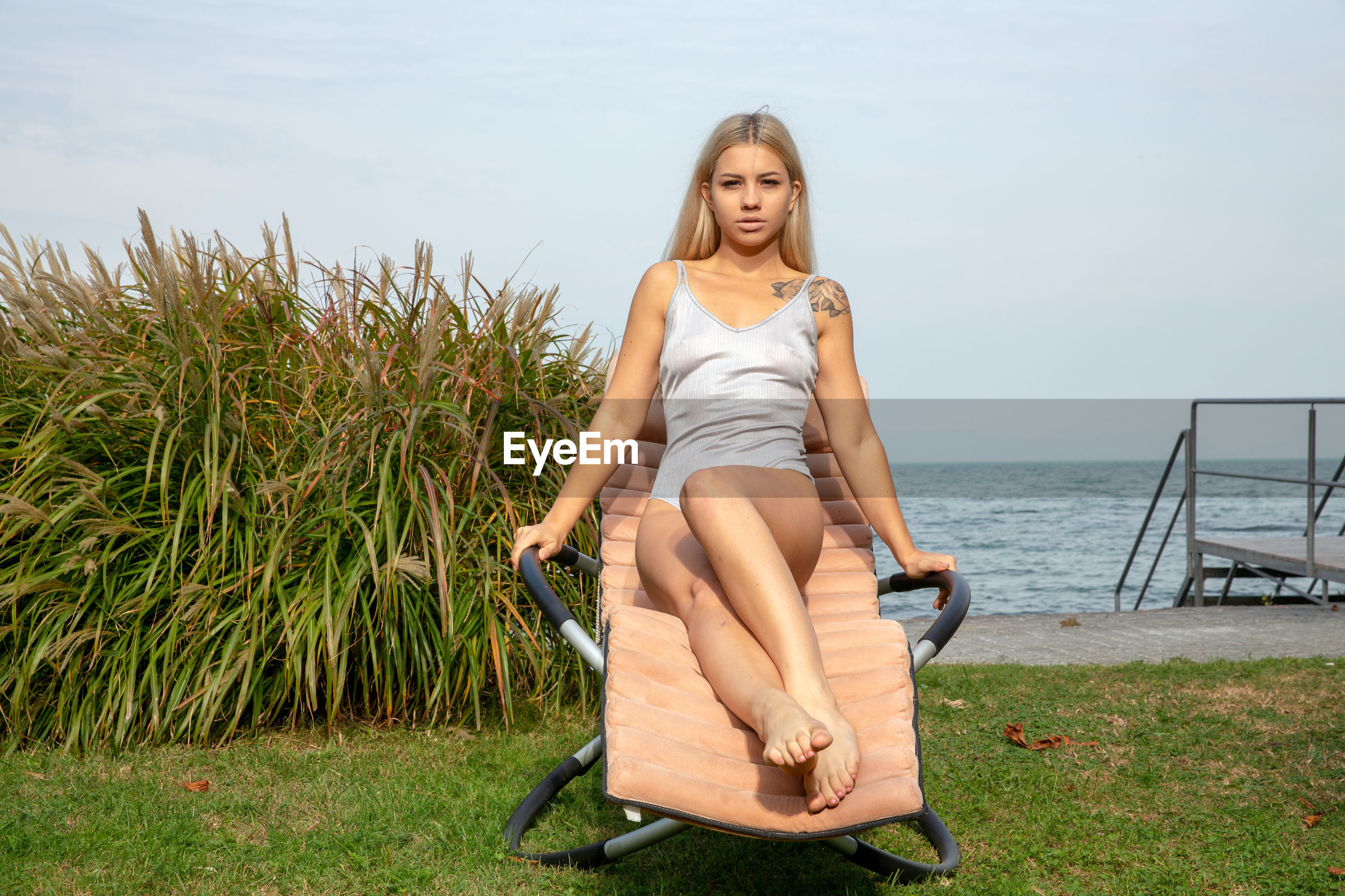 Portrait of beautiful young woman sitting on chair against sea and sky