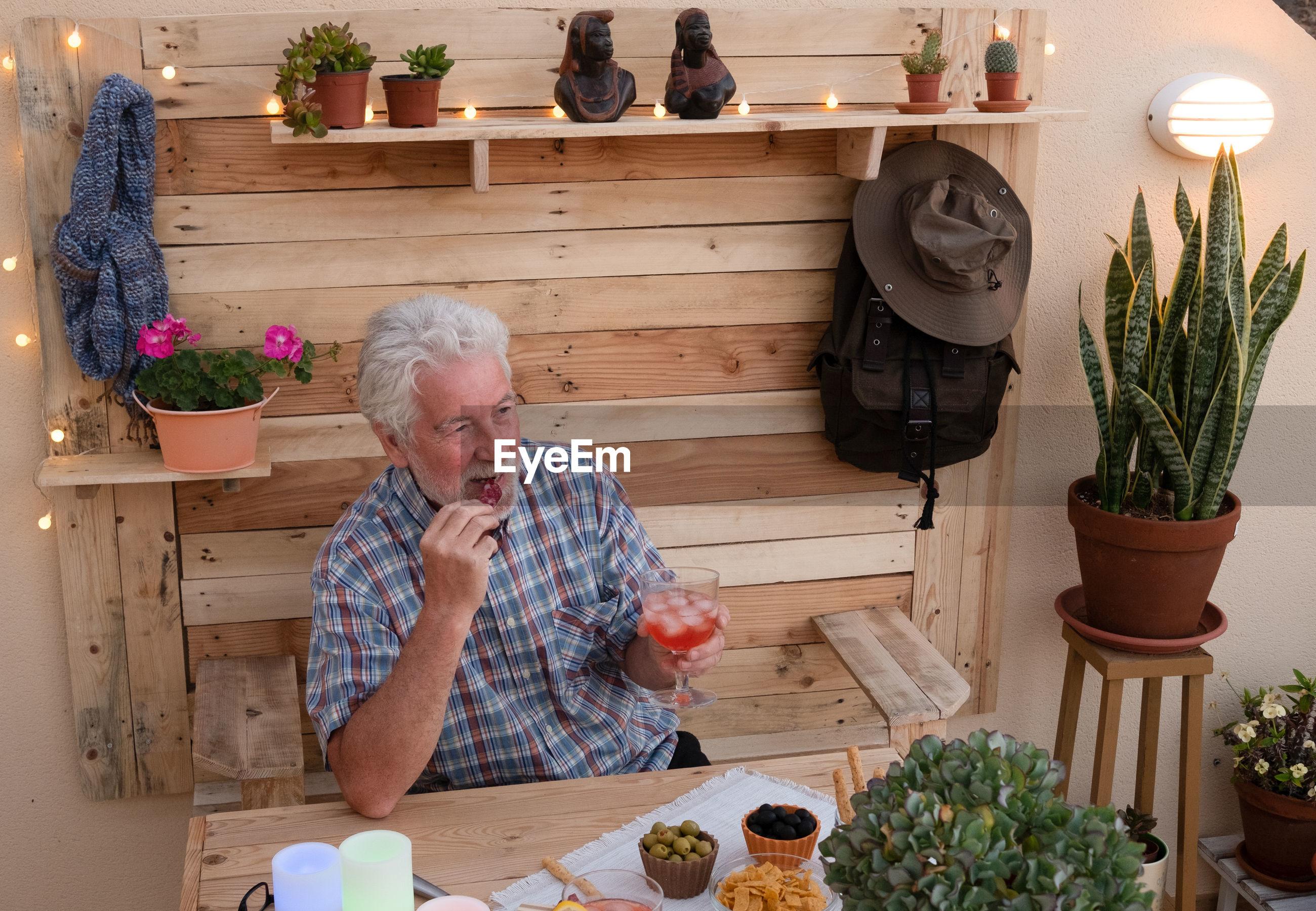 Senior man enjoying snacks and drink at building terrace