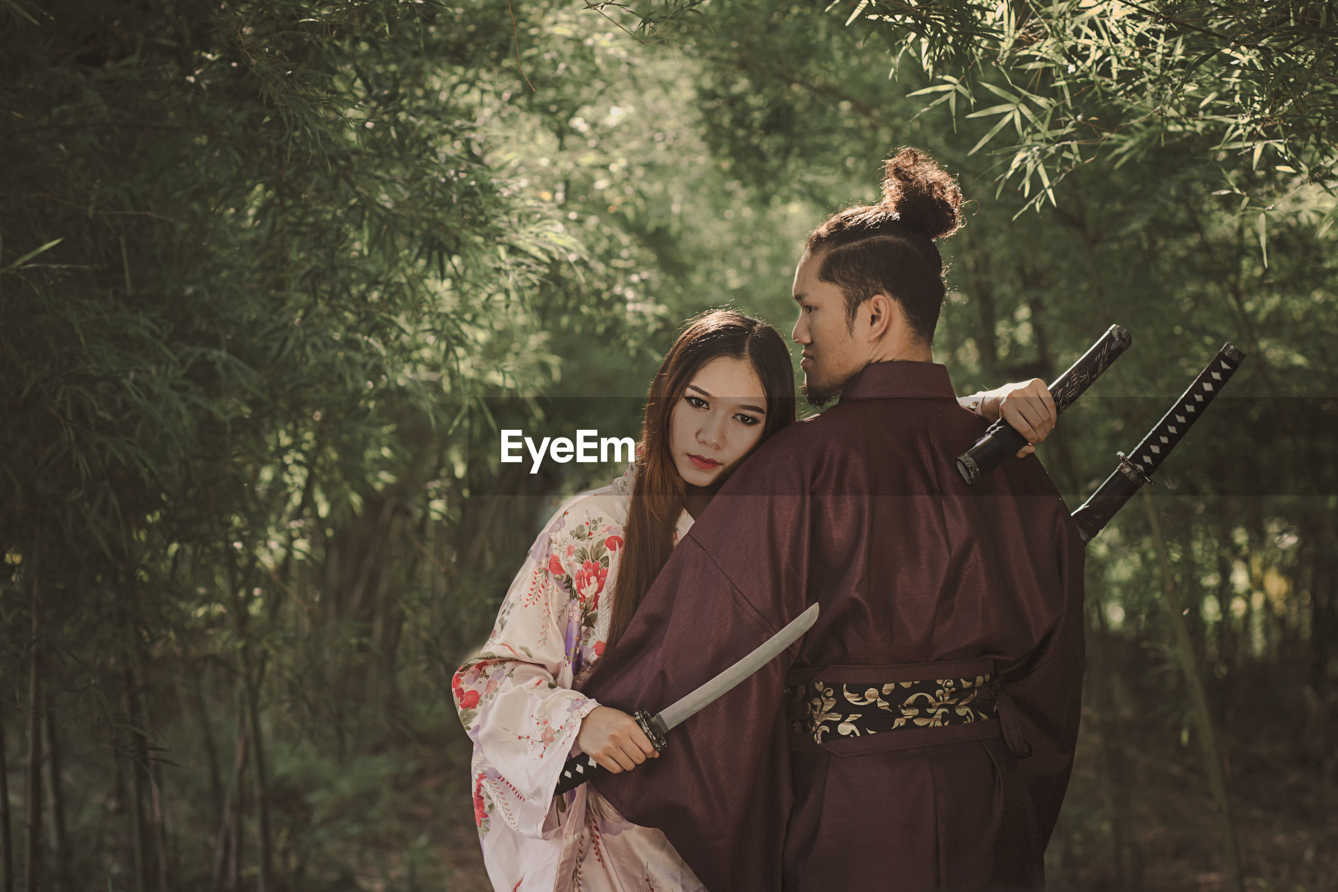 Couple with sword standing in forest