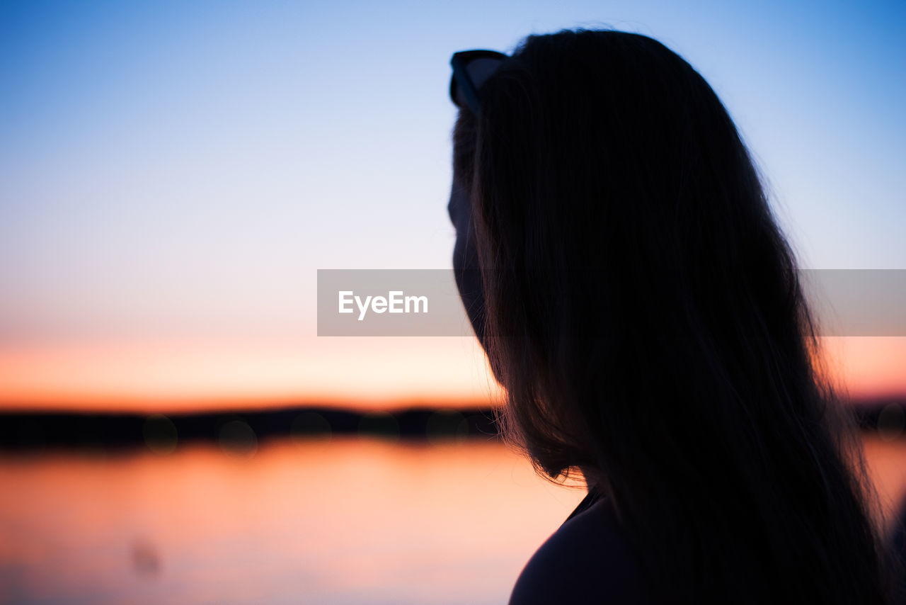 Side View Of Silhouette Teenage Girl Standing By Lake Against Sky During Sunset