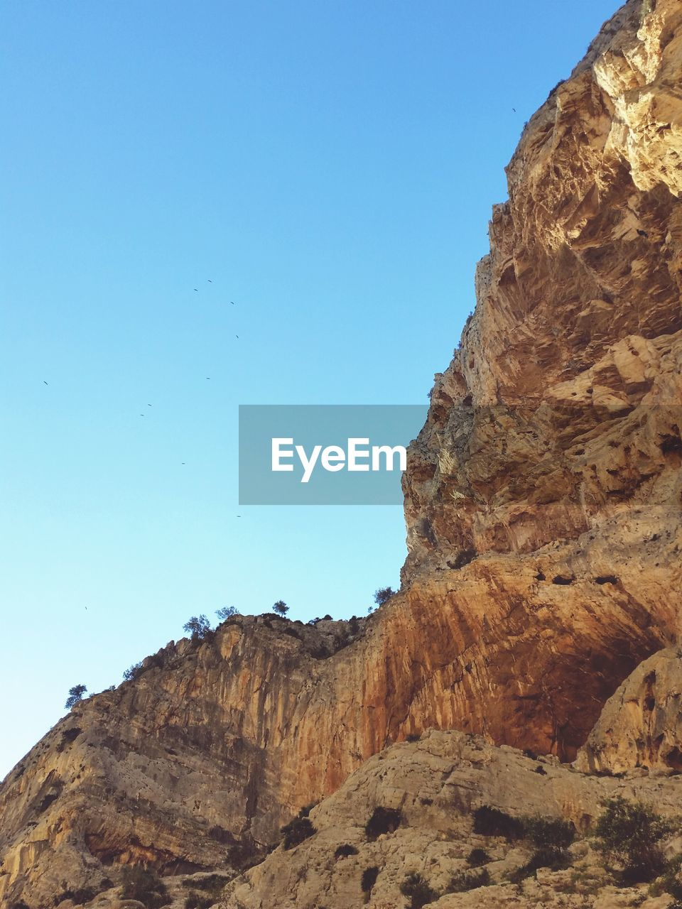 rock formation, rock - object, geology, nature, clear sky, blue, no people, tranquility, day, low angle view, beauty in nature, cliff, outdoors, mountain, sky