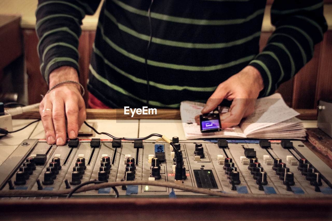 Midsection Of Man Using Sound Mixer