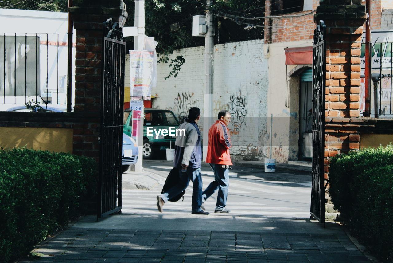 REAR VIEW OF MAN WALKING ON STREET BY BUILDINGS