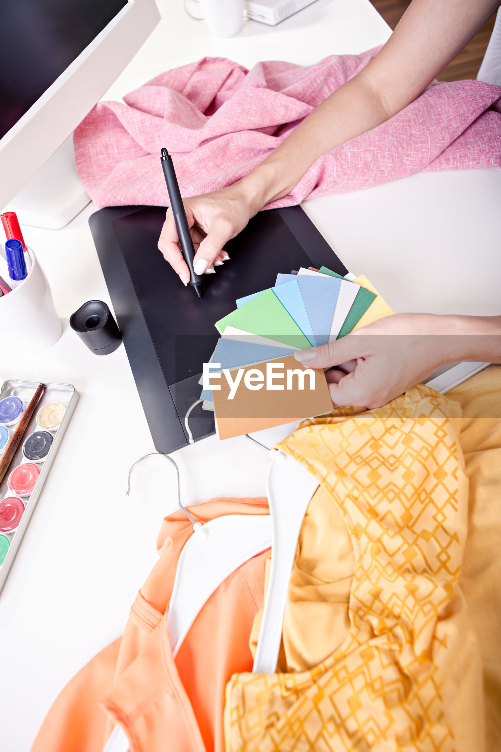 Midsection of woman with color swatches using graphics tablet on table