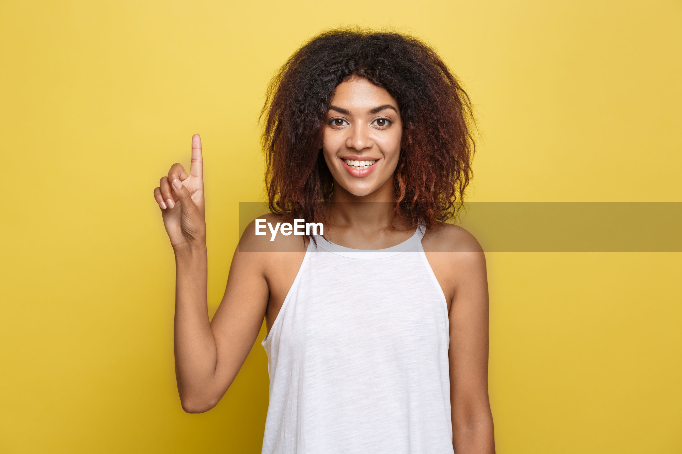 Portrait of smiling woman standing on yellow background