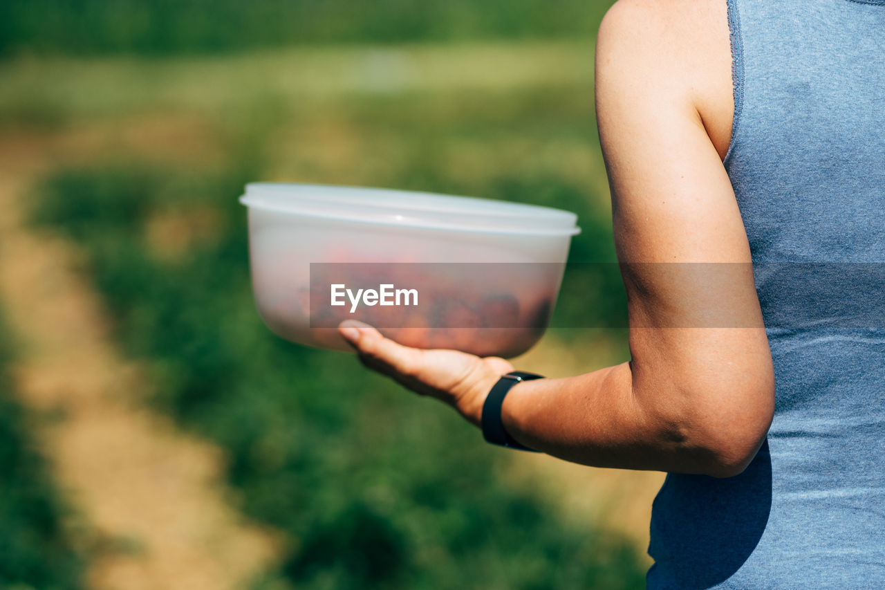 Cropped Image Of Woman Holding Strawberries In Container On Field