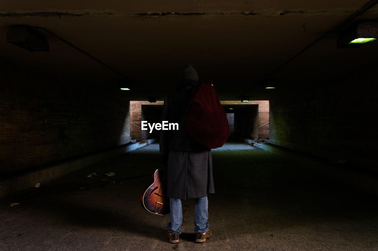 Rear View Of Man Standing In Underground Walkway