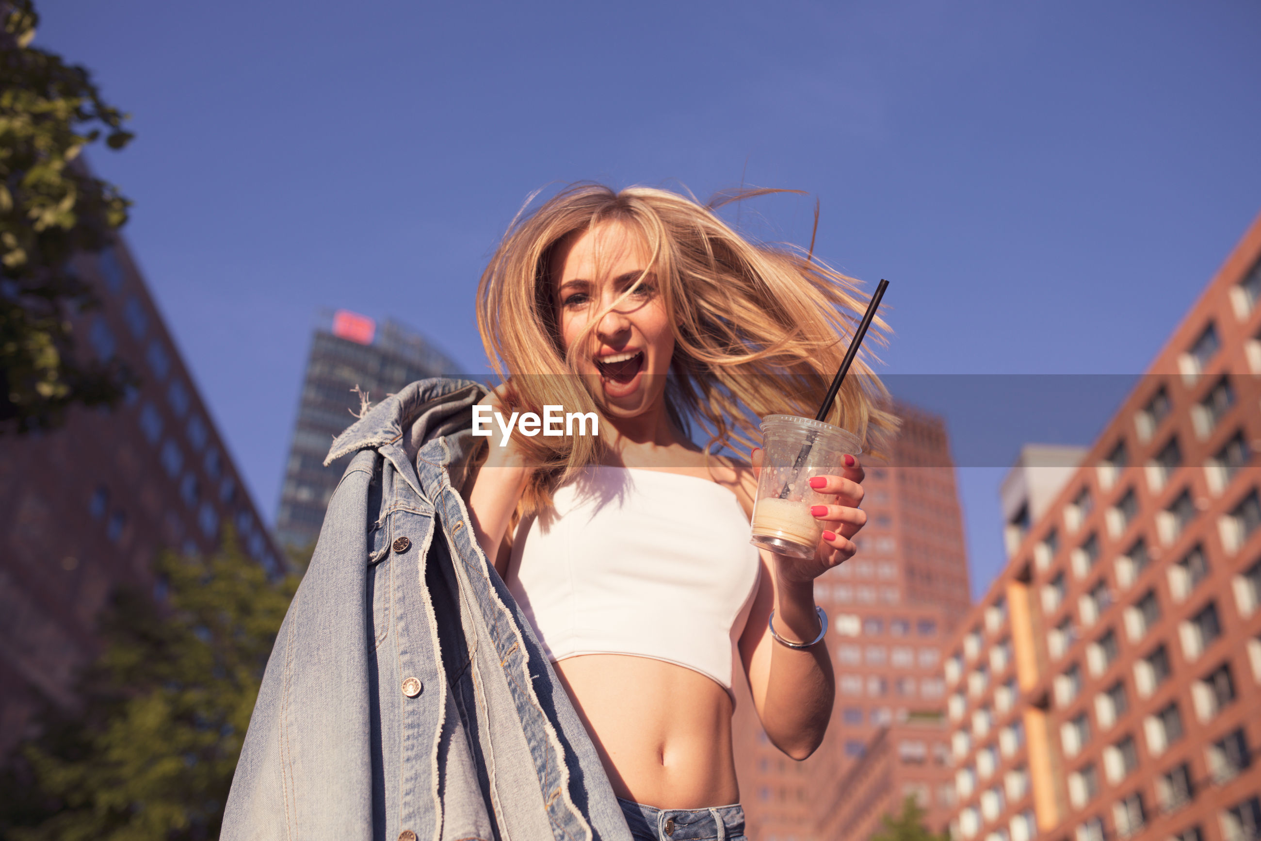 Low angle portrait of woman holding disposable cup against buildings