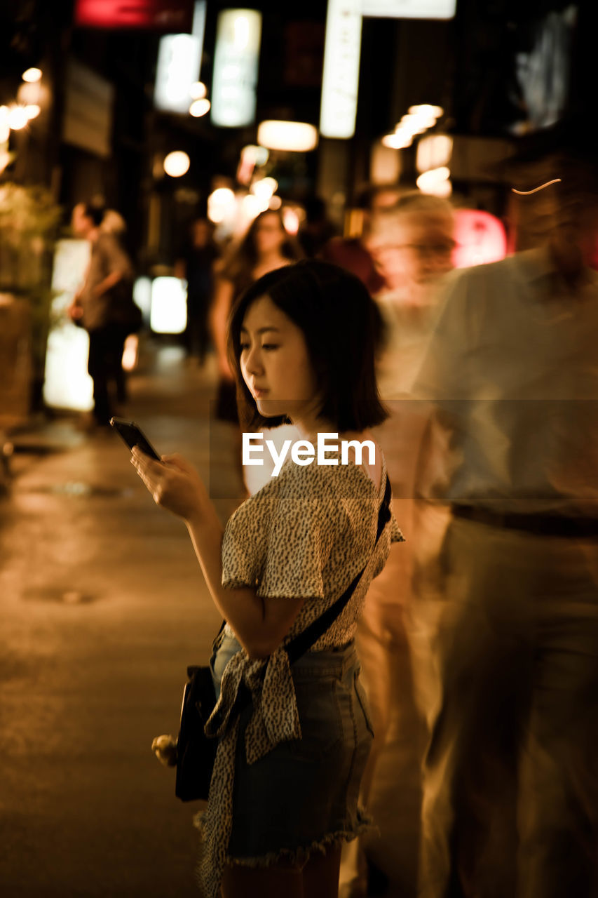 women, adult, real people, incidental people, lifestyles, standing, city, group of people, focus on foreground, leisure activity, illuminated, night, people, street, young adult, men, city life, motion, casual clothing, hairstyle