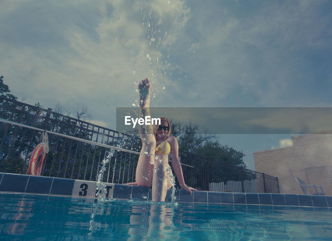 Woman Enjoying In Swimming Pool Against Sky