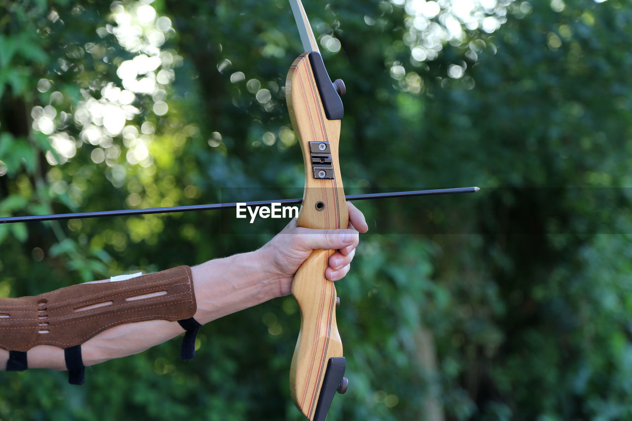 human hand, focus on foreground, hand, holding, day, one person, wood - material, real people, human body part, leisure activity, arrow - bow and arrow, tree, sport, plant, archery, aiming, nature, lifestyles, unrecognizable person, finger