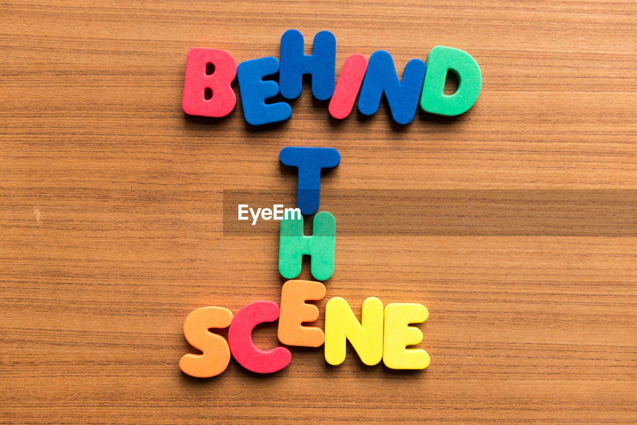 High angle view of colorful behind the scene text on wooden table