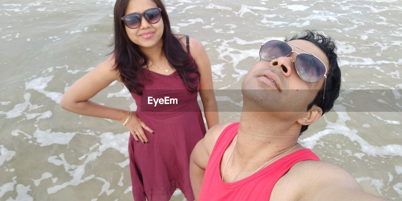 Portrait of couple in sunglasses at beach
