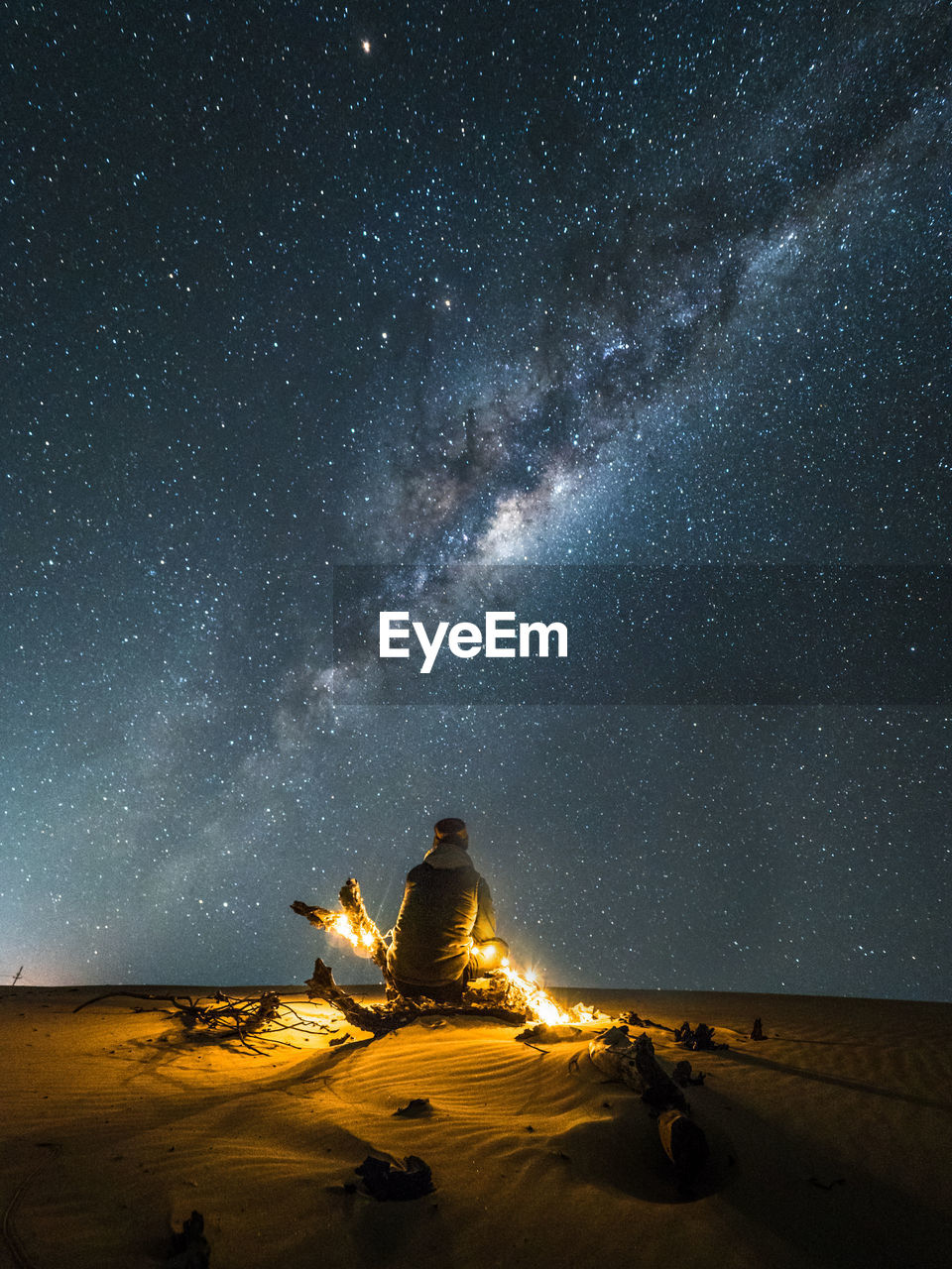 Rear View Of Man With Illuminated String Lights Sitting On Sand At Desert Against Star Field At Night