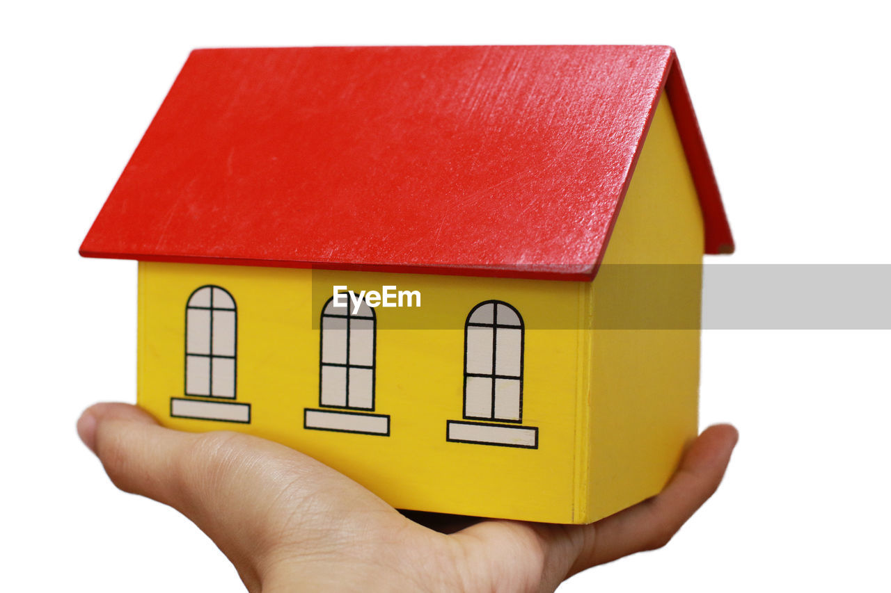 human hand, yellow, hand, human body part, one person, holding, white background, indoors, architecture, built structure, cut out, close-up, studio shot, house, unrecognizable person, red, building, body part, finger, small