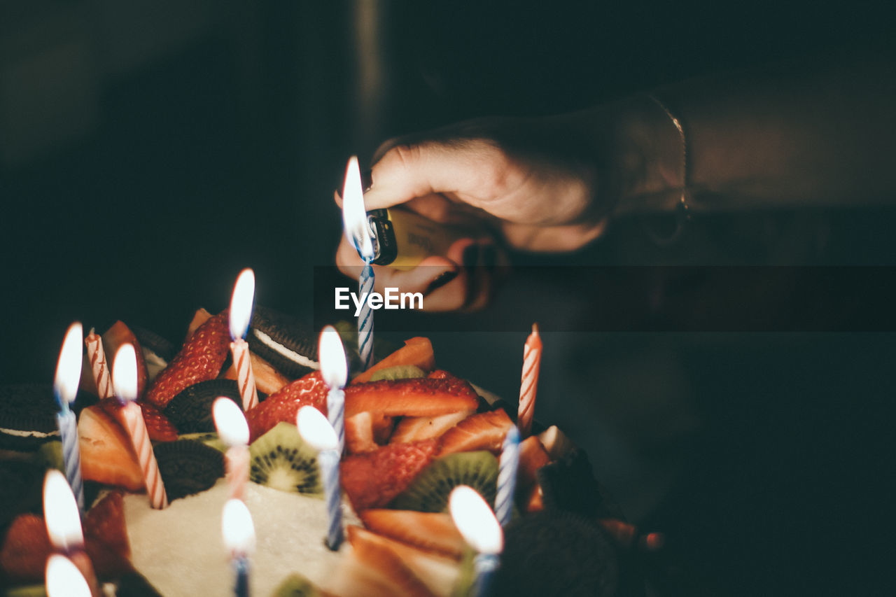Close-up of woman igniting candles on birthday cake