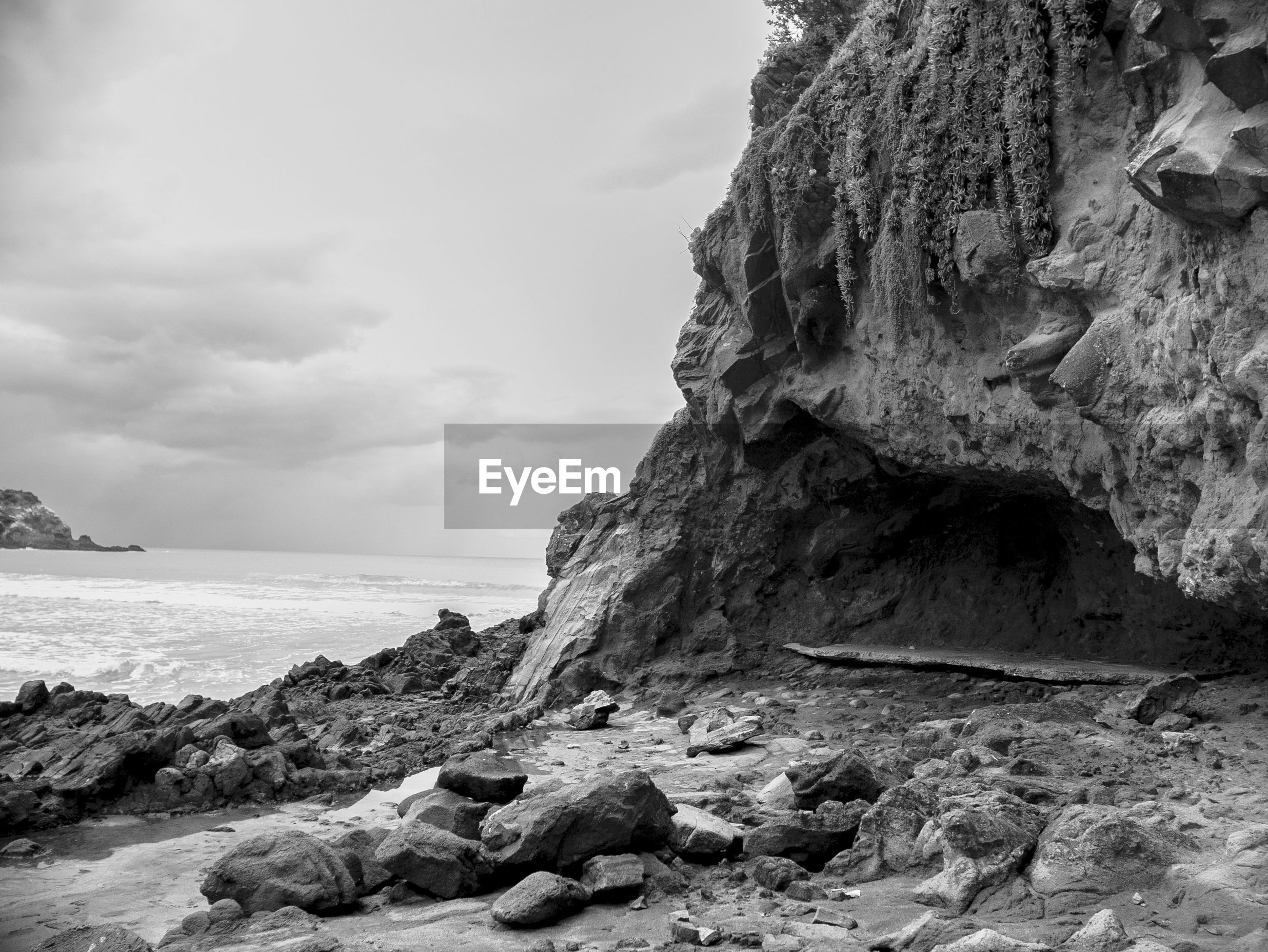 ROCK FORMATION ON SHORE AGAINST SKY