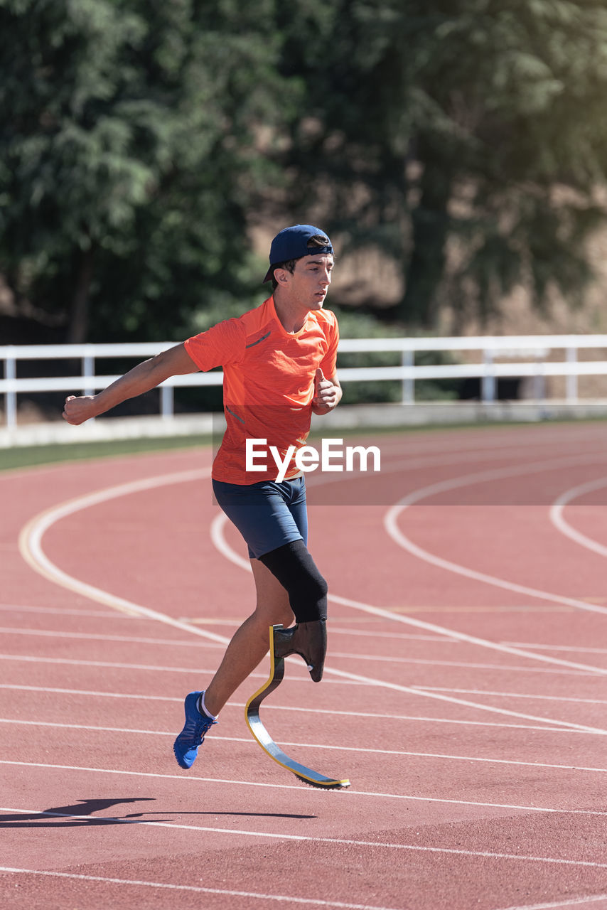 Young athlete with prosthetic leg running on sports track