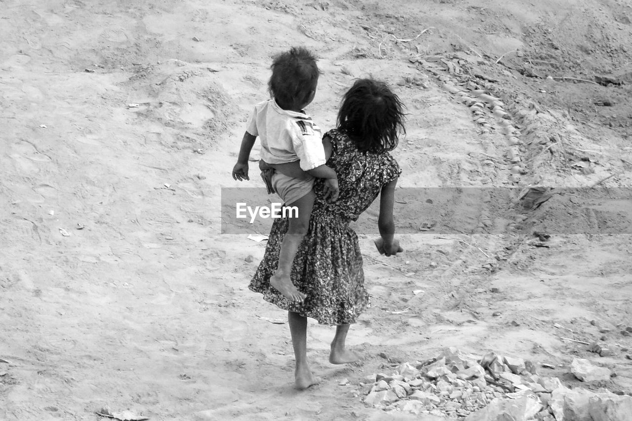 Girl Carrying Her Brother While Walking On Field