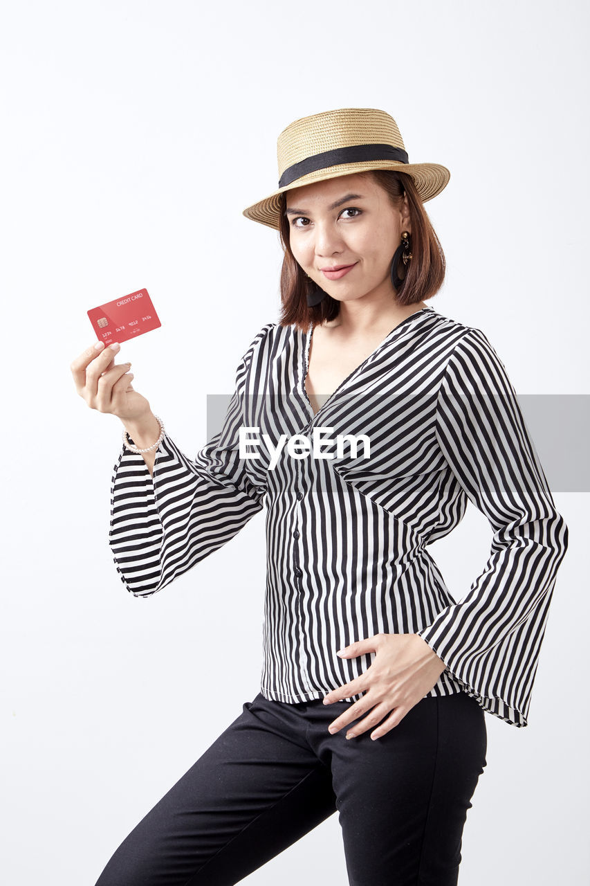 hat, one person, clothing, young adult, indoors, studio shot, three quarter length, young women, portrait, standing, white background, looking at camera, striped, front view, casual clothing, holding, women, cut out, adult, beautiful woman, hairstyle