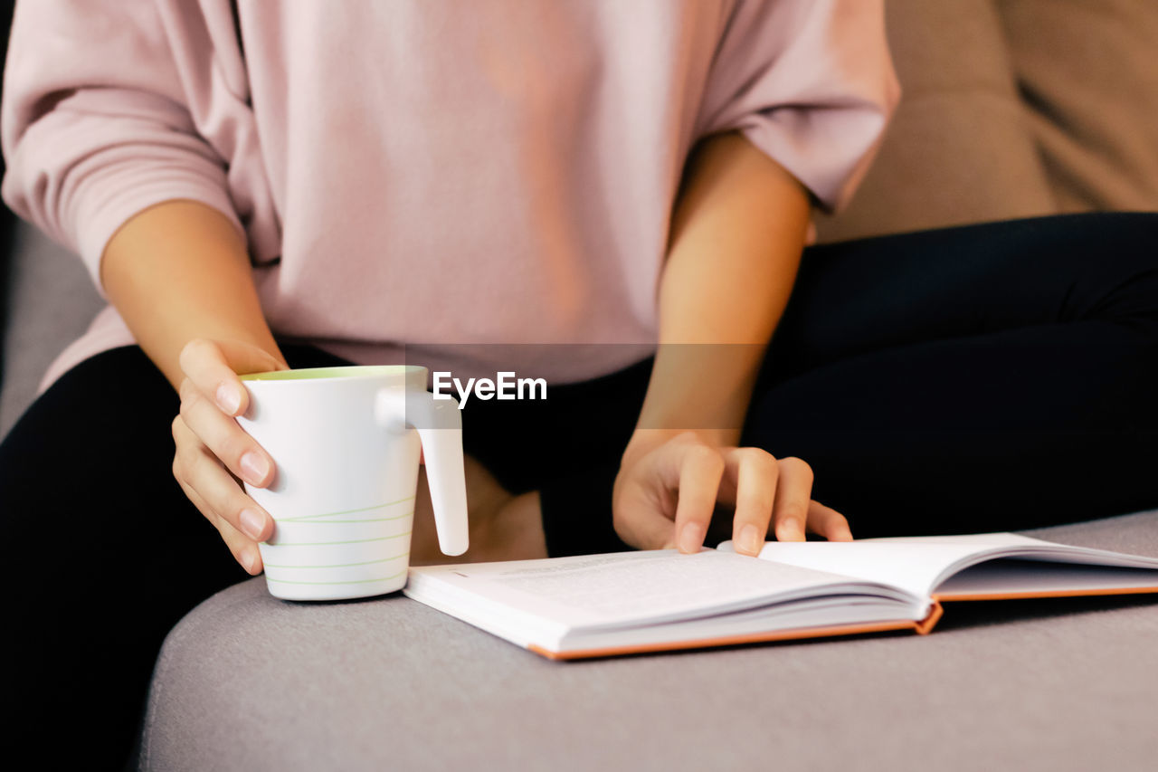 MIDSECTION OF WOMAN HOLDING COFFEE CUP AND BOOK