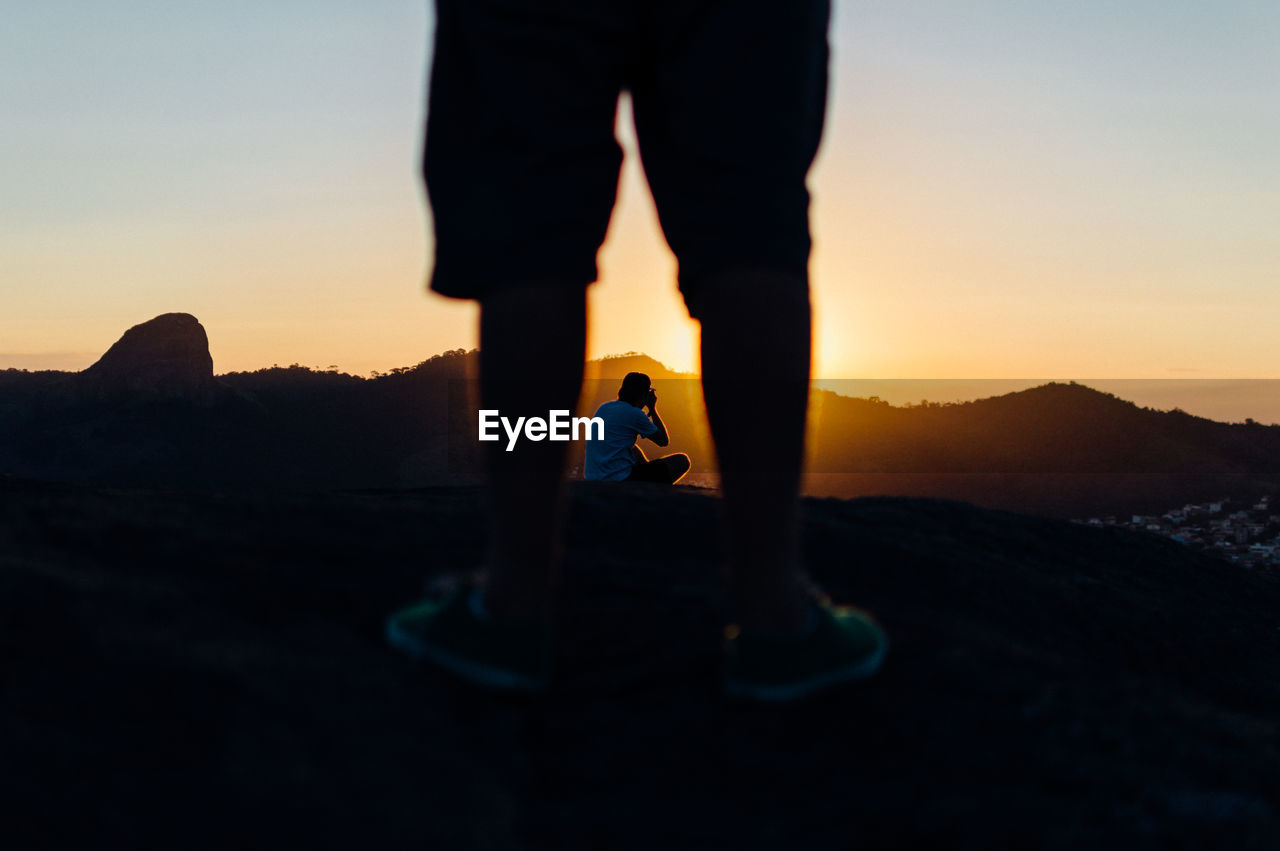 Low Section Of Man Standing On Rock Against Photographer During Sunset
