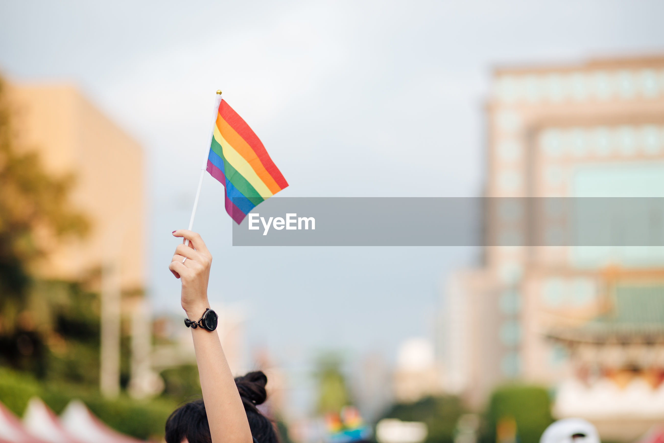 Cropped hand of woman holding rainbow flag against buildings