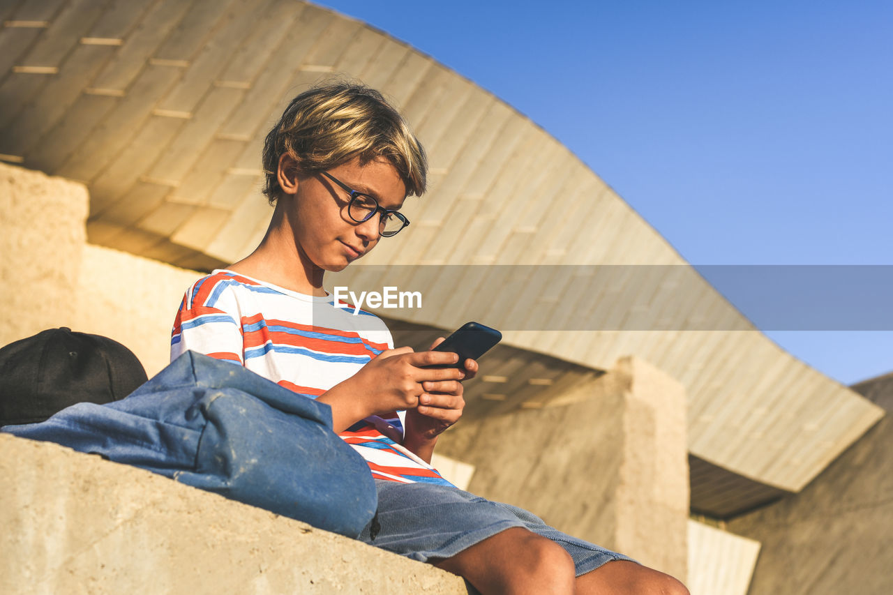 Low angle view of boy using phone while sitting outside building