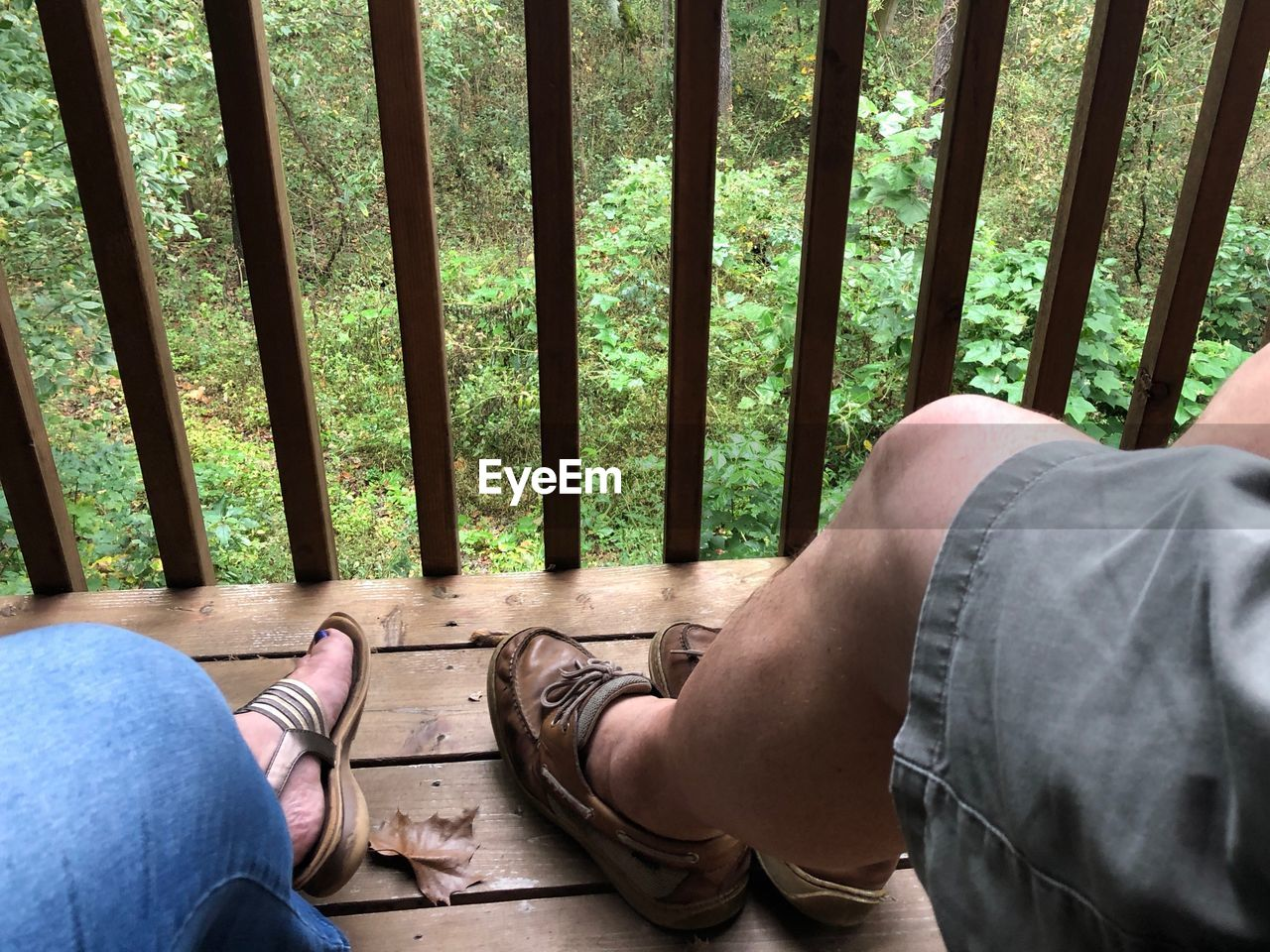 real people, human leg, human body part, low section, body part, men, day, lifestyles, people, personal perspective, jeans, leisure activity, two people, sitting, casual clothing, relaxation, togetherness, high angle view, indoors, human foot