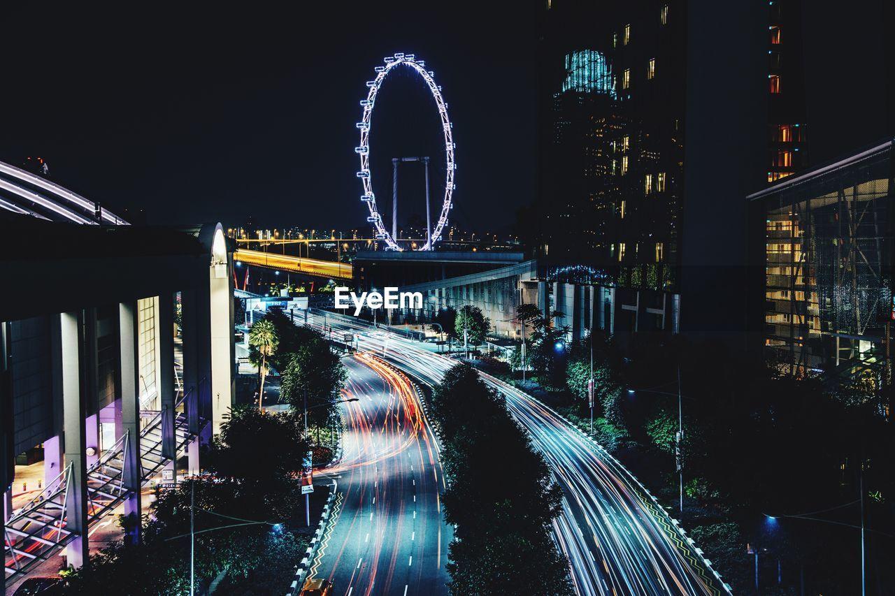 LIGHT TRAILS ON ROAD AGAINST ILLUMINATED CITY AT NIGHT