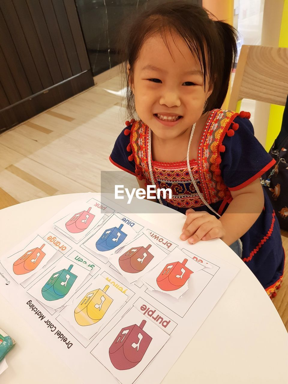 Portrait of cute smiling girl sitting by chart on table
