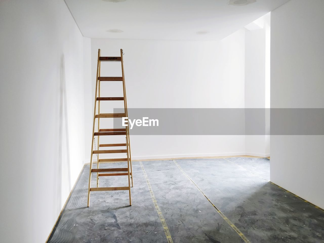 Empty white room with ladder being renovated